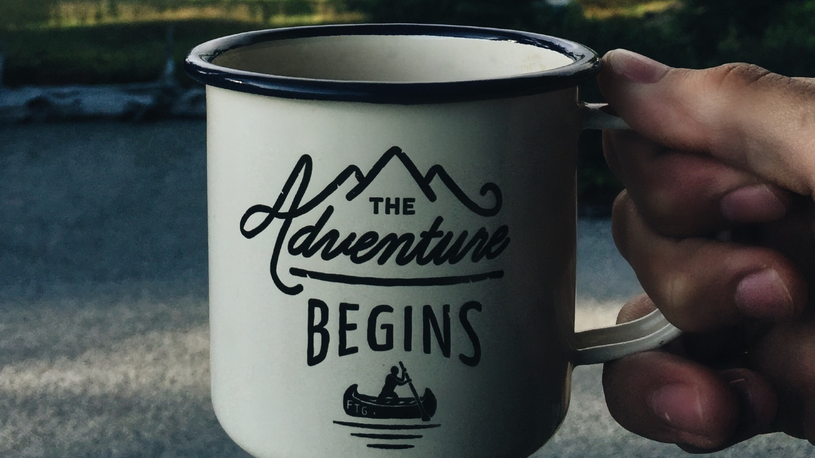 "Cup bearing the label ""The adventure begins"""