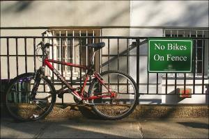 Fahrrad, das trotz eines Verbotsschildes an einen Zaun angeschlossen ist